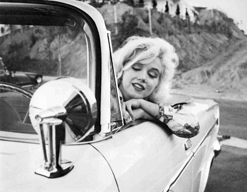 Marilyn Monroe riding around in a convertible in style.