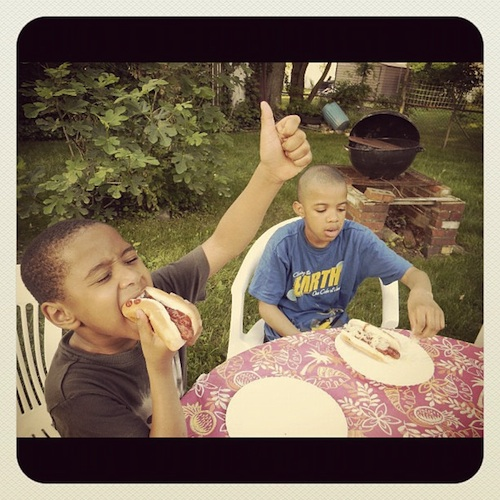 Two african american boys eating hotdogs outside during the summer
